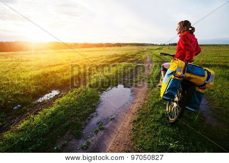 Lady hiker standing on the wet road with loaded bicycle