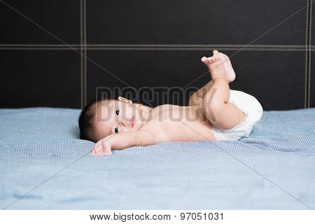 Cute Asian Baby Lying On A White Pillow, On Bed