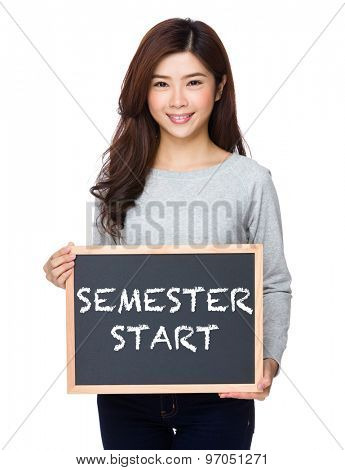 School girl hold with chalkboard and showing phrase of semester start