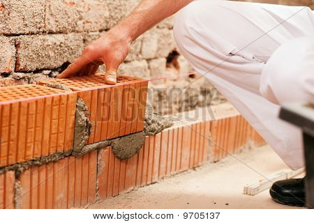bricklayer making wall with brick and grout