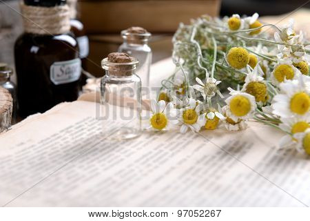 Old book with dry flowers and bottles on table close up