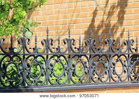 Elegant Wrought Metal Fence Painted With Black Paint Against A Brick Wal