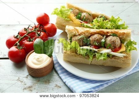 Homemade Spicy Meatball Sub Sandwich on plate, on wooden table background