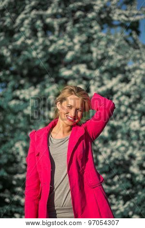 beautiful woman in a pink coat in blooming gardens
