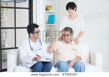 Doctor and patient. Asian old man headache, consult family doctor, sitting on sofa. Senior retiree indoors living lifestyle.