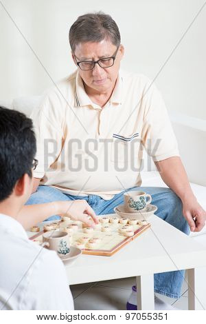 Chinese family, senior father and adult son playing Chinese chess (Xiang Qi) at home.