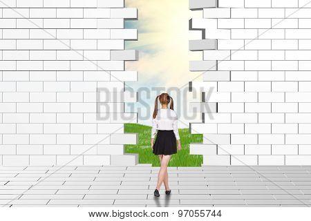 Schoolgirl watching dilapidated brick wall