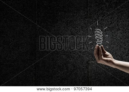 Human hand on dark background holding light bulb