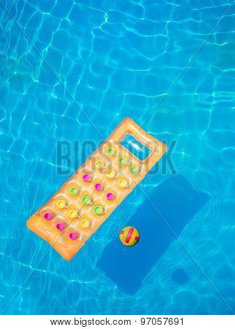 Floating orange air mattress in swimming pool