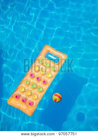 Floating orange air mattress in swimming pool