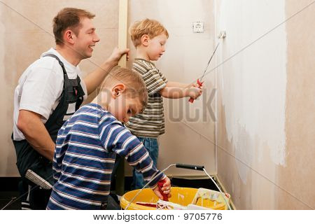 Father painting wall with children