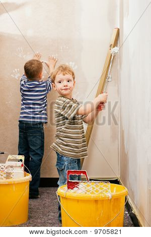 Two children painting wall at home
