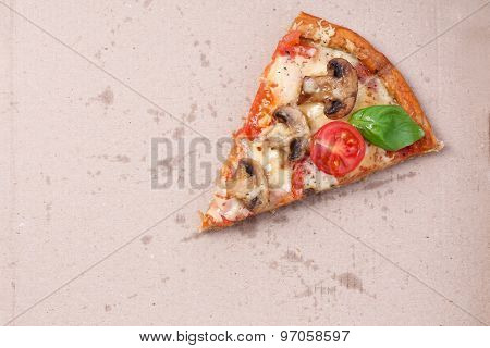 Slice of tasty pizza with vegetables and basil in cardboard close up