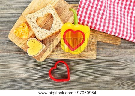 Bread slice with cut in shape of heart and pepper on table close up