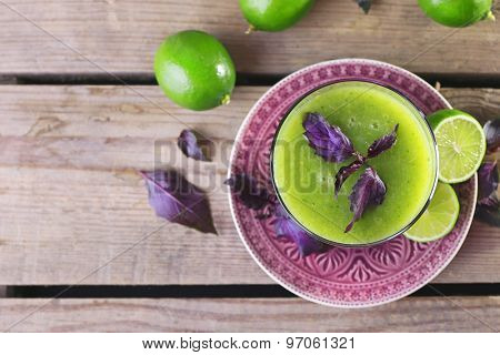 Glass of green healthy juice with basil and limes on table close up