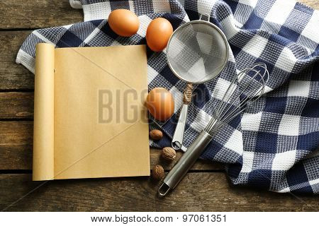 Open recipe book, eggs and napkin on wooden background