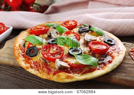 Tasty pizza with vegetables and basil on table close up
