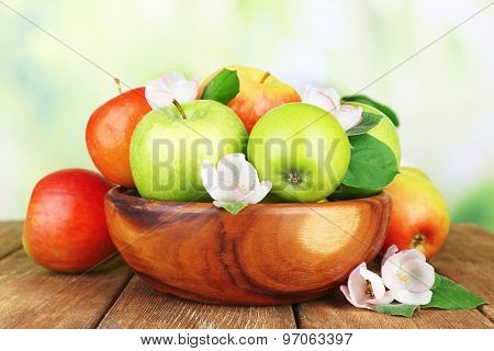 Fresh apples with apple blossom in bowl, on wooden table, on nature background