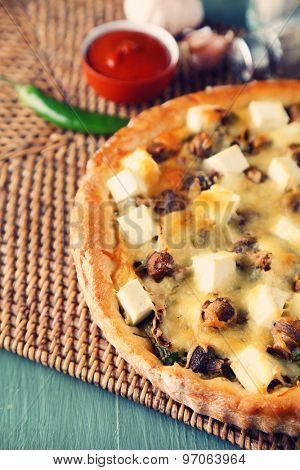 Cheese pie with mushrooms, herbs and sour creme, on wicker mat, on wooden table background
