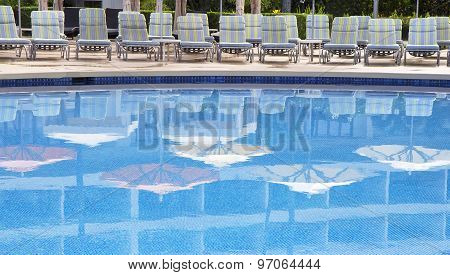 Swimming Pool With Umbrellas Reflections