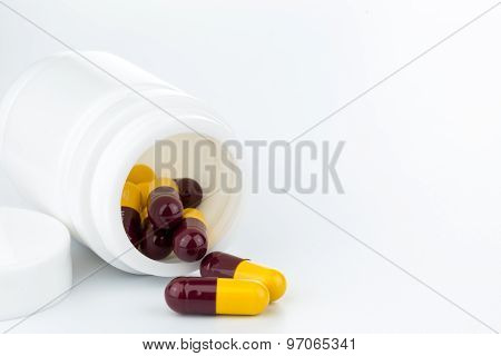Brown And Yellow Pills An Pill Bottle On White Background
