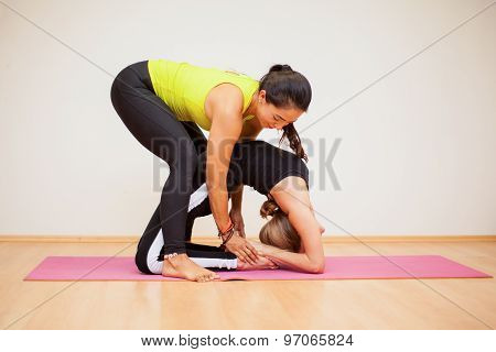 Yoga Instructor Assisting A Student