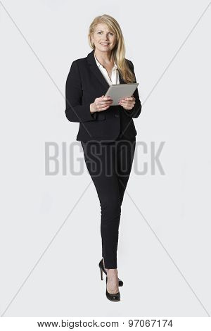 Studio Portrait Of Mature Businesswoman Holding Digital Tablet
