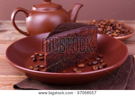 Delicious chocolate cake with coffee beans on plate on table close up