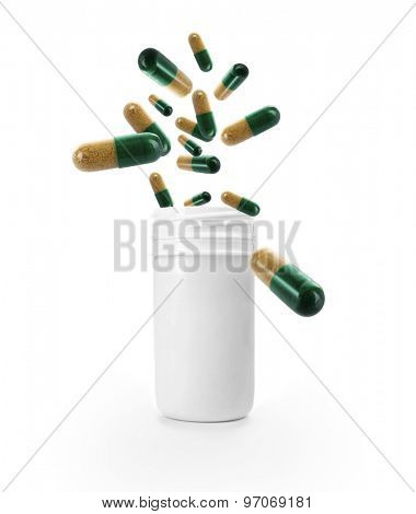 Bright pills flying away from open plastic bottle isolated on white