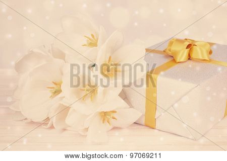Beautiful bouquet of white tulips and gift box on table on light background