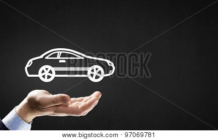 Hand of businessman with car against gray background