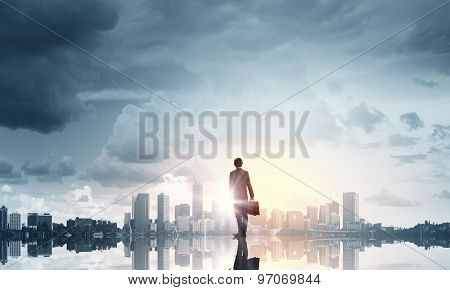 Businessman standing with back and looking at sunrise above city