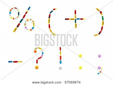 Different signs made with pills isolated on white
