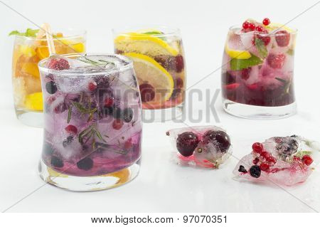Summer Refreshment Next To Frozen Fruit In Ice Cubes On White Background