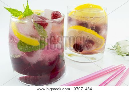 Natural Homemade Red Forest Fruit Iced-t Juice With Ice, Lemon And Sliced Fruits In A Crooked Glass