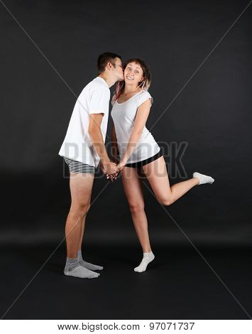 Funny young couple on black background
