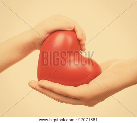 Heart in child and mother hands on light background