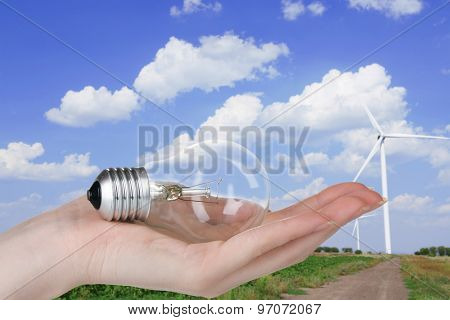 Light bulb in hand on windmills field background