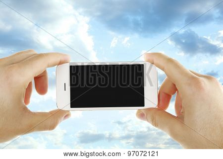 Hands holding mobile smart phone on sky background