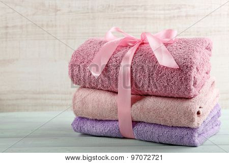 Stack of colorful towels on light background