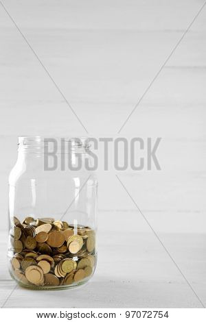 Coins in money jar on wooden background
