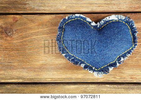 Denim heart on wooden background
