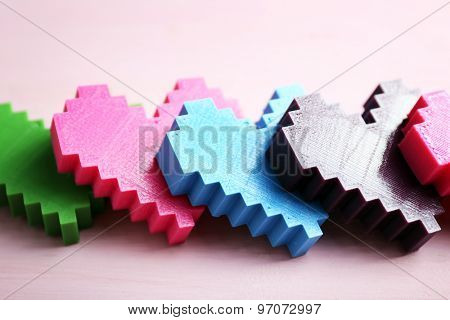 Plastic hearts on wooden table, closeup