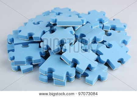 Pile of blue puzzle pieces, closeup