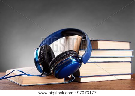 Books and headphones as audio books concept on grey background