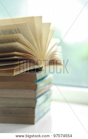 Books on white windowsill, close up