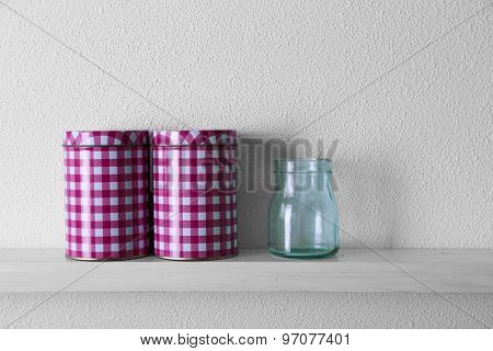Decorative vases on wooden shelf  on white wallpaper background