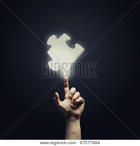 Human hand pointing with finger at puzzle element