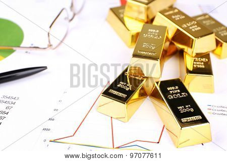 Gold bullion with coins on documents background