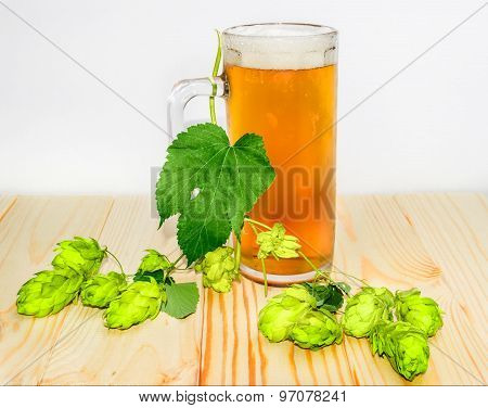 Mug Of Beer And Branch Of Hops On Wooden Surface